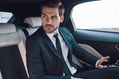 Young and successful. Handsome young man in full suit looking away while sitting in the car royalty free stock images