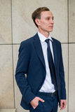 Young and successful. Handsome young businessman looking away while walking outdoors with office building in background. Young and successful. Handsome young Royalty Free Stock Photos