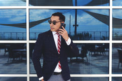 Young successful intelligent men entrepreneur having telephone conversation while standing near office window outdoors Royalty Free Stock Image