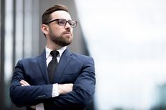 Stylish man crossing hands. Young successful male in business dress, eyeglasses crossing hands, looking away on blurred background royalty free stock images
