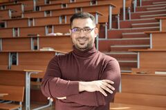 Free Young Successful Male Teacher Of University Crossing His Arms By Chest While Standing In Auditorium Royalty Free Stock Photos - 215817398