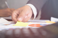 Young successful man holding sticky note paper on meeting in mod Royalty Free Stock Images