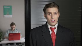 Young successful man in a suit shows an emotion of doubt, uncertain, portrait. Man works on a computer in the background stock footage