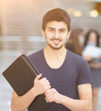 Young successful manager with a folder in his hands, background of the work of his team. Young successful manager with a folder in his hands, in the background Royalty Free Stock Images