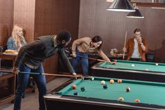 young successful multiculture friends playing in pool