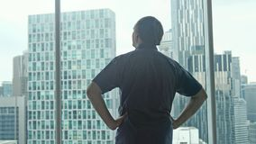 Young successful rich man unveil curtains and admire the city center with skyscrapers view. Young man unveil curtains and admire cityscape view royalty free stock photos