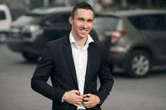 Young successful smiling man in a black suit, on the street, on the background of cars. Happy modern man. Outdoors stock photo