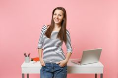 Young successful woman holding hands in pockets work and standing near white desk with pc laptop isolated on pastel pink stock images