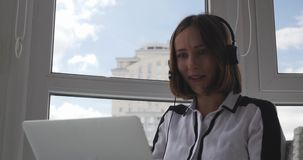 Young successful woman in strict clothes and headphones sitting in modern office and speaking by webcam at video conference with h stock video footage