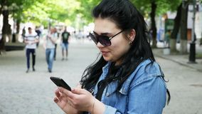 Young successful woman uses a mobile phone. On the street, people on background stock video footage