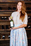 A young successful woman winemaker, businessman. A young successful woman winemaker demonstrates his wine cellar and its wine products, concept business Royalty Free Stock Photo