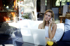Young suceessful woman entrepreneur talking on mobile phone while work on portable laptop computer, Stock Photo