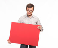 Young sullen man showing presentation, pointing on placard Royalty Free Stock Photography