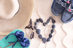 Young summer love at the beach. In a conceptual image with a straw sunhat, slip slops and boys shoes surrounding a pebble heart on golden beach sand with a Stock Photo