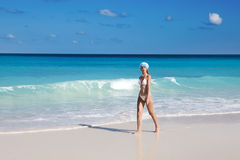 The young suntanned slender woman with a long fair hair in bikini goes on a peschenny beach against turquoise ocean Royalty Free Stock Photo