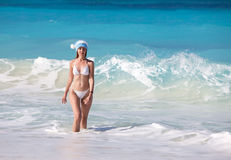 The young suntanned slender woman with in white sexual bikini goes on a peschenny beach against turquoise ocean Stock Images