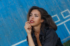 Young suntanned woman in a short top and shirt with beautiful modern make-up and hair posing against blue wooden wall Royalty Free Stock Photography