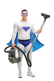 Young superhero holding a vacuum cleaner Stock Image