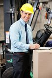 Young Supervisor Writing On Clipboard At Warehouse. Portrait of young male supervisor writing on clipboard by a forklift at warehouse Stock Photos