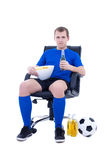 Young supporter in football form sitting with ball, chips and bo Royalty Free Stock Photos