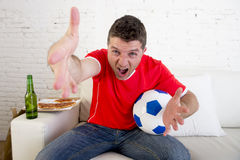 Young supporter man with ball and beer bottle watching football game on television sitting at home couch Stock Image