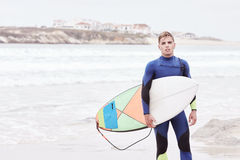 Young surfer on beach. Portrait of young athletic male surfer wearing blue wetsuit, holding surfboard under his arm, standing on beach after morning surfing Royalty Free Stock Photography