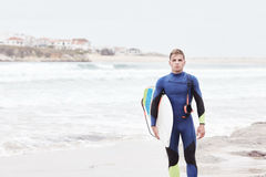 Young surfer on beach. Portrait of young athletic male surfer wearing blue wetsuit, holding surfboard under his arm, standing on beach after morning surfing Stock Photography