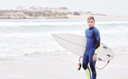 Young surfer on beach. Portrait of young athletic male surfer wearing blue wetsuit, holding surfboard under his arm, standing on beach after morning surfing Royalty Free Stock Images