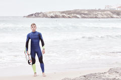 Young surfer on beach. Portrait of young athletic male surfer wearing blue wetsuit, holding surfboard under his arm, standing on beach after morning surfing Stock Image