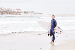 Young surfer on beach. Portrait of young athletic male surfer wearing blue wetsuit, holding surfboard under his arm, standing on beach after morning surfing Royalty Free Stock Image