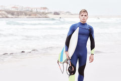 Young surfer on beach. Portrait of young athletic male surfer wearing blue wetsuit, holding surfboard under his arm, standing on beach after morning surfing Stock Photo