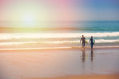 young surfer couple going into the ocean at sunrise Stock Photos