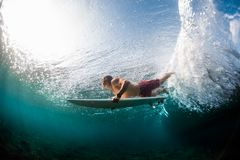 Young surfer dives under the ocean wave. And performs trick named in surfing as a Duck Dive Stock Images