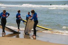 Young surfer friends in wetsuits walking along the shore Stock Photos