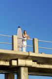 Young surfer girl standing on pier with surfboard Stock Images