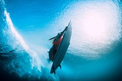 Young surfer girl with surfboard dive underwater with fun under big ocean wave. stock images