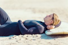 I need some rest. A young surfer with his board on the beach Royalty Free Stock Photos