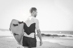 Young surfer holding his surfboard on the beach - Handsome man waiting waves for surfing - Black and white editing royalty free stock image