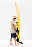 Young surfer holding surfboard and looking over his shoulder. Back view a young surfer holding surfboard and looking over his shoulder isolated on the white Royalty Free Stock Photography