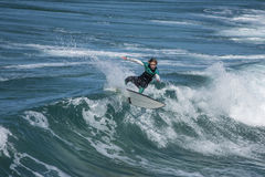 Young surfer re-enters the crest of a wave Stock Photo