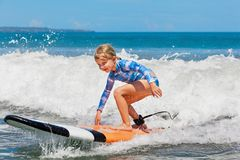 Young surfer rides on surfboard with fun on sea waves Royalty Free Stock Photography
