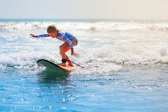 Young surfer rides on surfboard with fun on sea waves royalty free stock photo