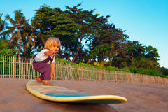 Young surfer stand on surfboard with fun on sunset beach Stock Images