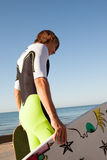 Young surfer about to get into the sea Stock Images