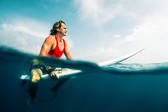 Young surfer waits wave in the ocean. At sunny day. Split shot with underwater view Stock Photos