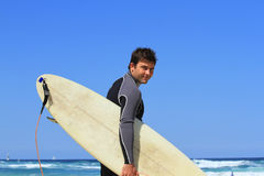 Young surfer. Walking to the surf and turning to look on camera Royalty Free Stock Image
