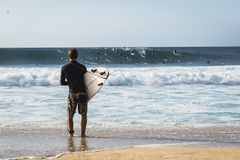 Young surfer is watching other people surfing big waves. Banzai Pipeline, Oahu, Hawaii / USA - Febrary 21 2018: Young surfer is watching other people surfing big Royalty Free Stock Photo