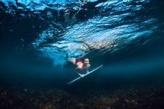 Young surfer woman dive underwater with under wave stock photo