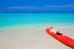 Young surfer woman at white beach on red surfboard Royalty Free Stock Images