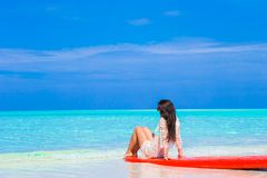Young surfer woman at white beach on red surfboard Stock Photo